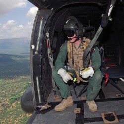 A Royal Air Force aircrewman sits in the back of a Puma helicopter during Exercise Askari Thunder over Northern Kenya.