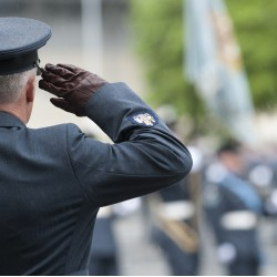 A Royal Air Force Station Warrant Officer salutes the Old Colours during a Parade.